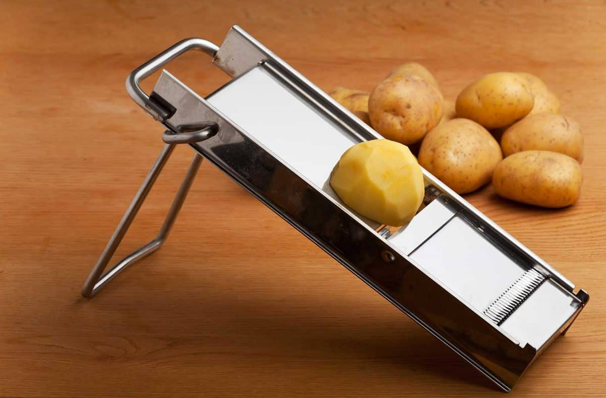 Half a potato on a mandolin slicer