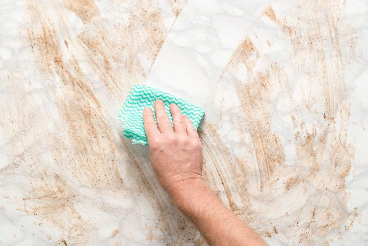 Hand wiping clean a dirty marble surface with a paper towel