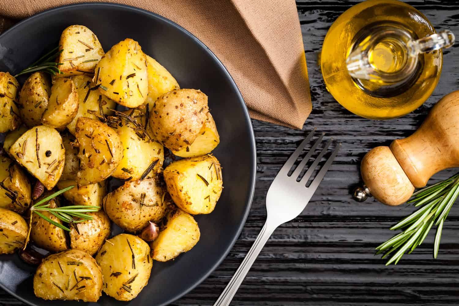 Huge sliced deep fried potatoes with oregano leaves and olive oil on the side