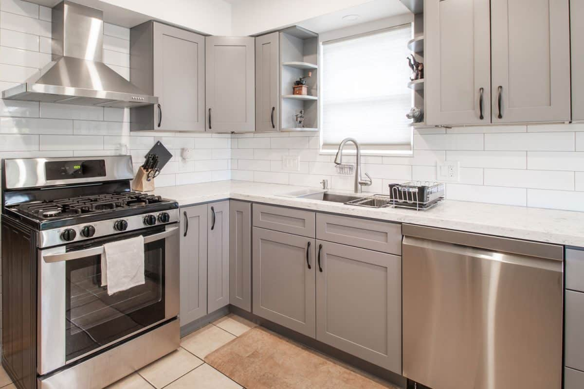 Interior of a modern kitchen with gray colored cabinet panels, a kitchen range with a hood, and a white tiled plank backsplash, How To Protect Kitchen Cabinet Doors From Water Damage