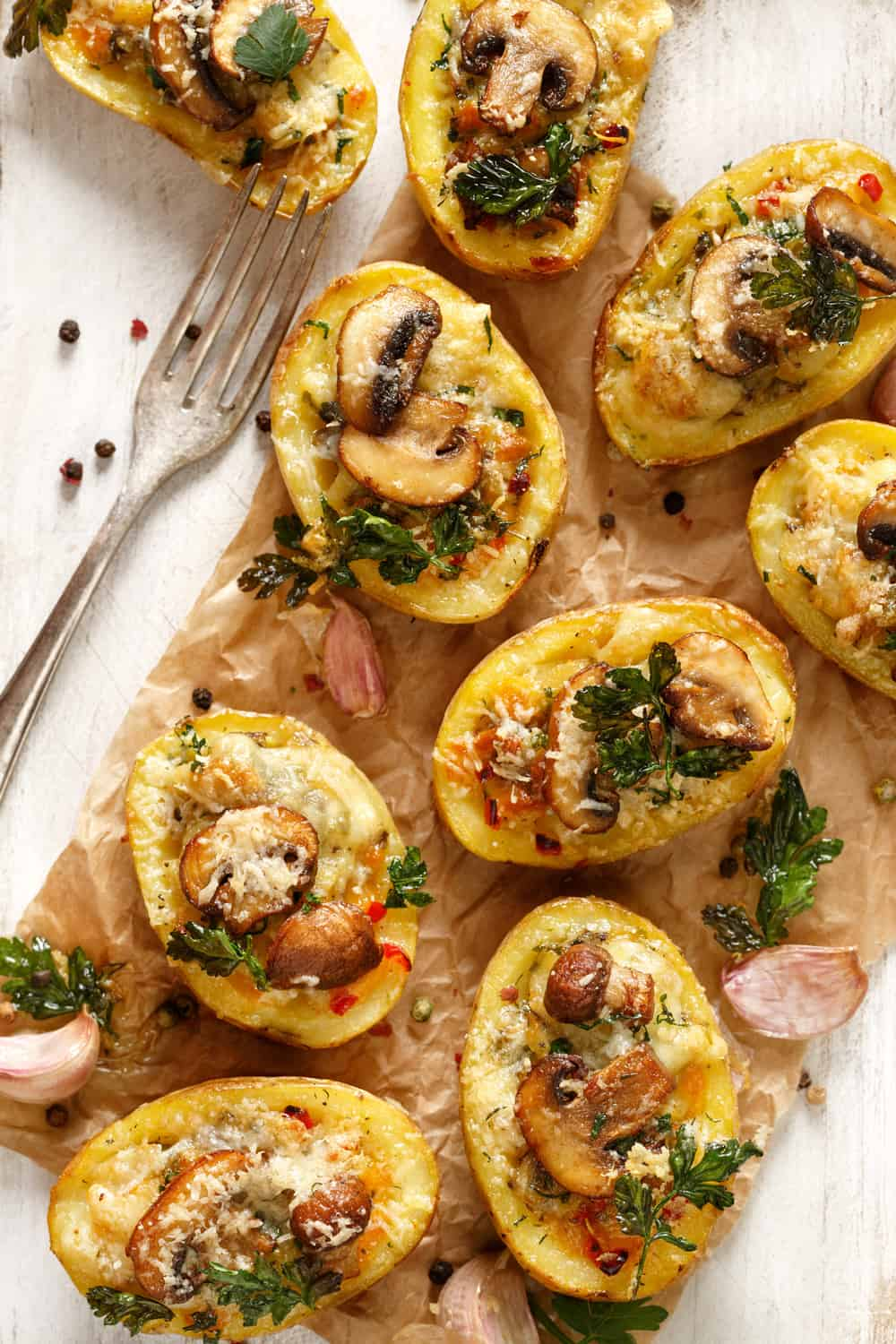 Loaded vegetarian twice-baked potatoes on white wooden table