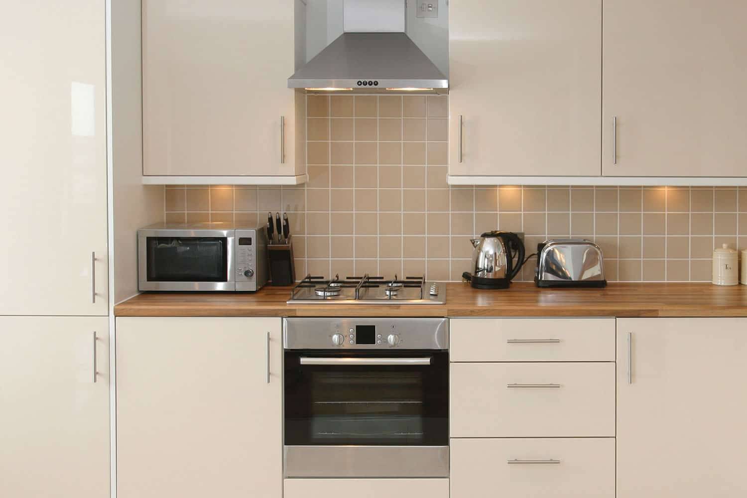 Modern kitchen interior with inegrated appliances and ceramic tiled walls and floor, How Many Inches Should There Be Between The Stove And Microwave?