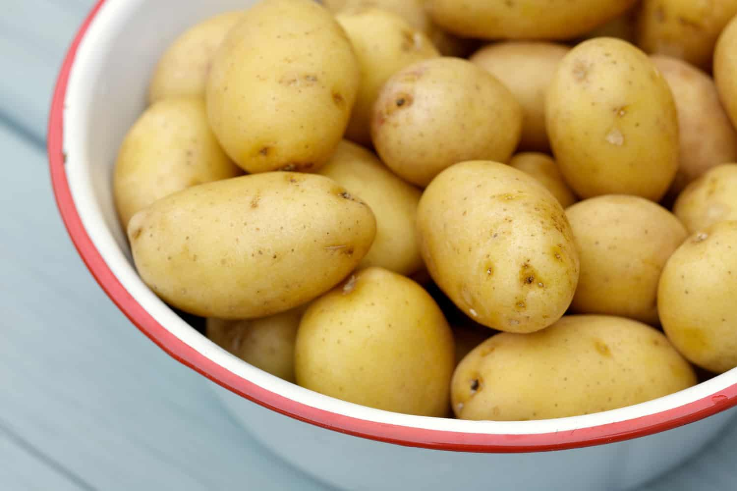 Natural light photo of raw small potatoes in metal bowl on wood table