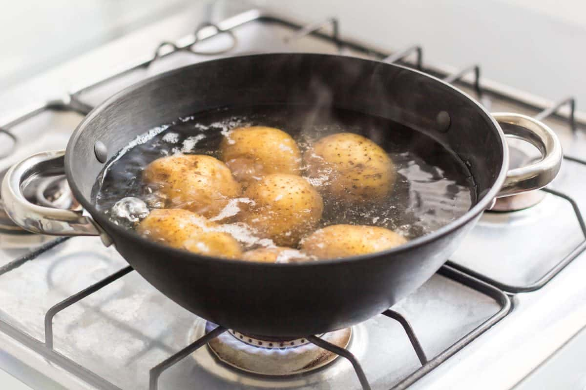 Potatoes placed inside a sauce pan under boiling water, Should You Peel And Cut Potatoes Before Or After Boiling?