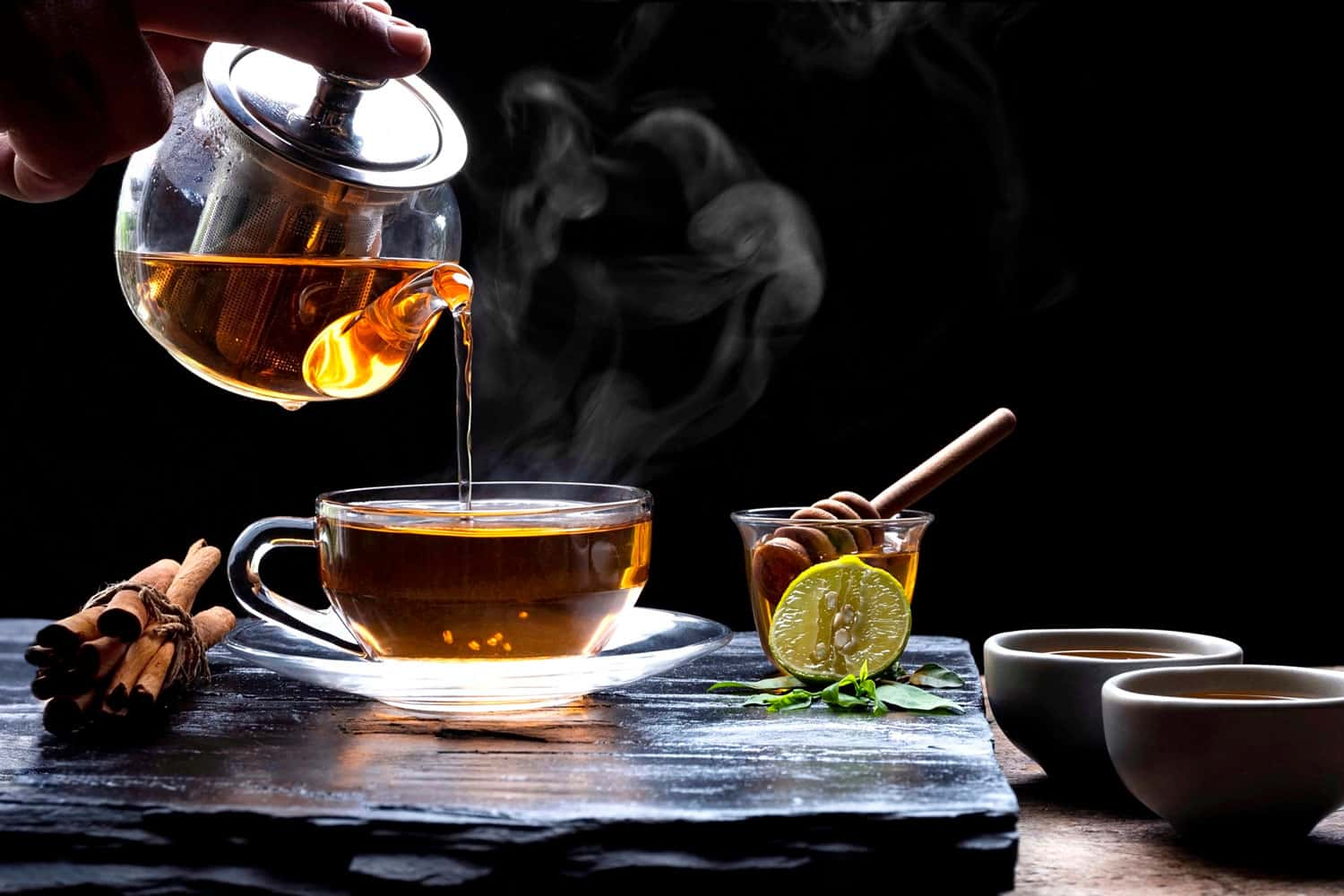 Pouring hot aromatic herbal tea from teapot into glass teacup set with steam and various herbs on black stone plate with wooden table floor in dark background, 5 Best Saucepans For Making Tea