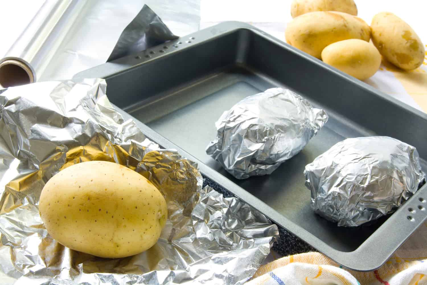Preparation of baked potatoes. Potatoes are being wrapped in aluminum foil.