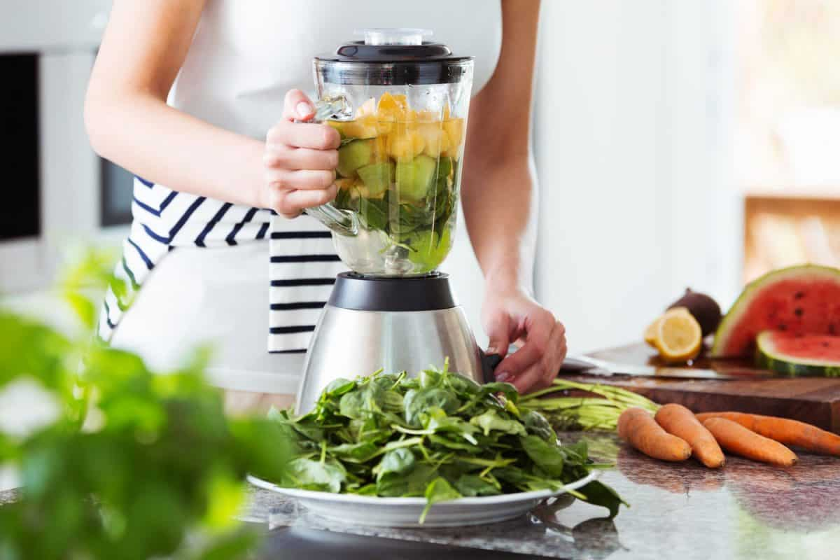 Vegetarian preparing vegan smoothie with rucola, citrus, cucumber in kitchen with carrots on countertop, Blender Won't Turn On - What To Do?
