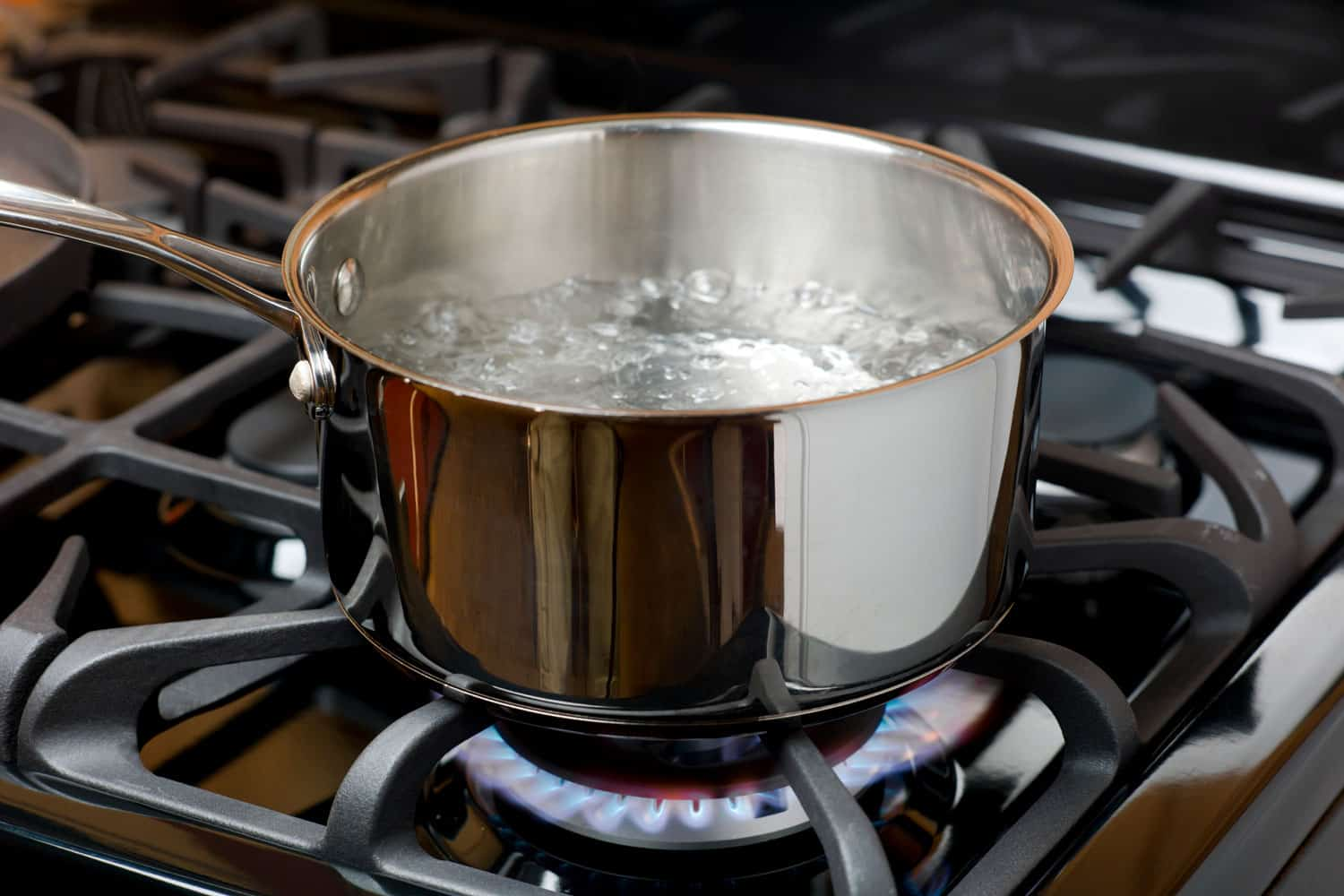 Water bubbles and boils on a gas stove or range in a home kitchen
