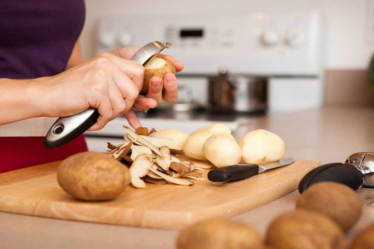 Young woman peeling potatoes in the kitchen of her home