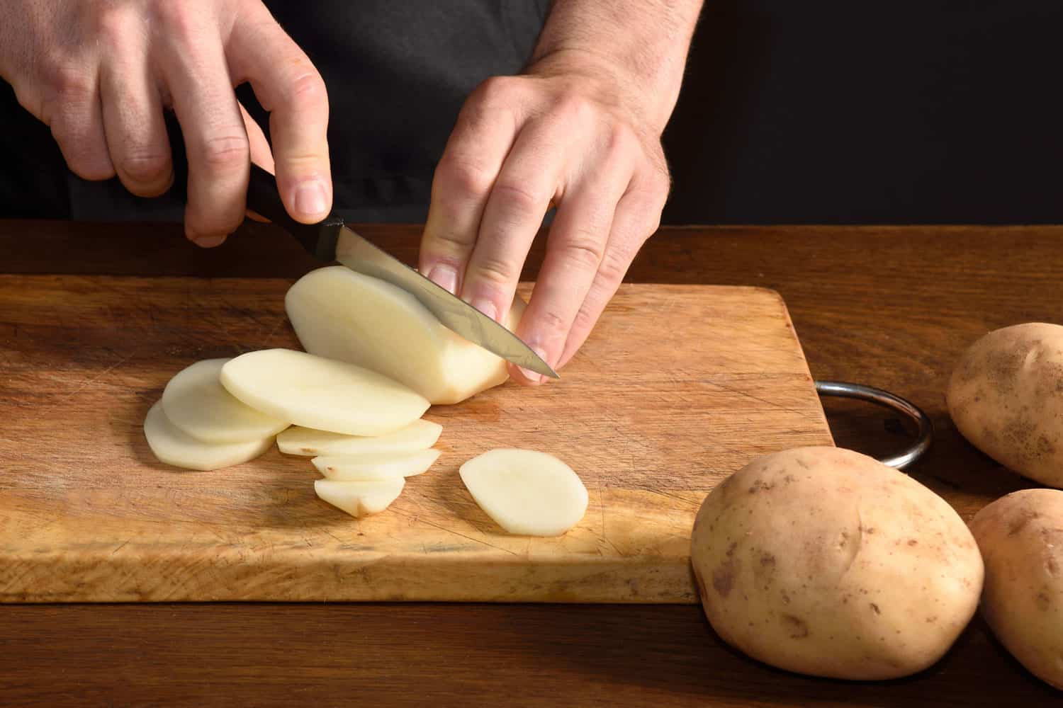 detail of a chef slicing potatoes