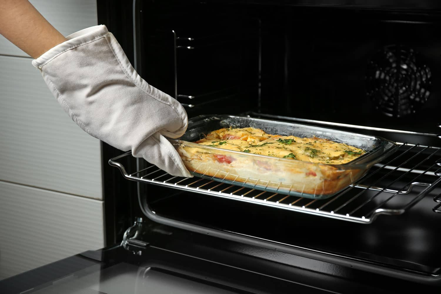 A woman taking a freshly baked lasagna off the oven