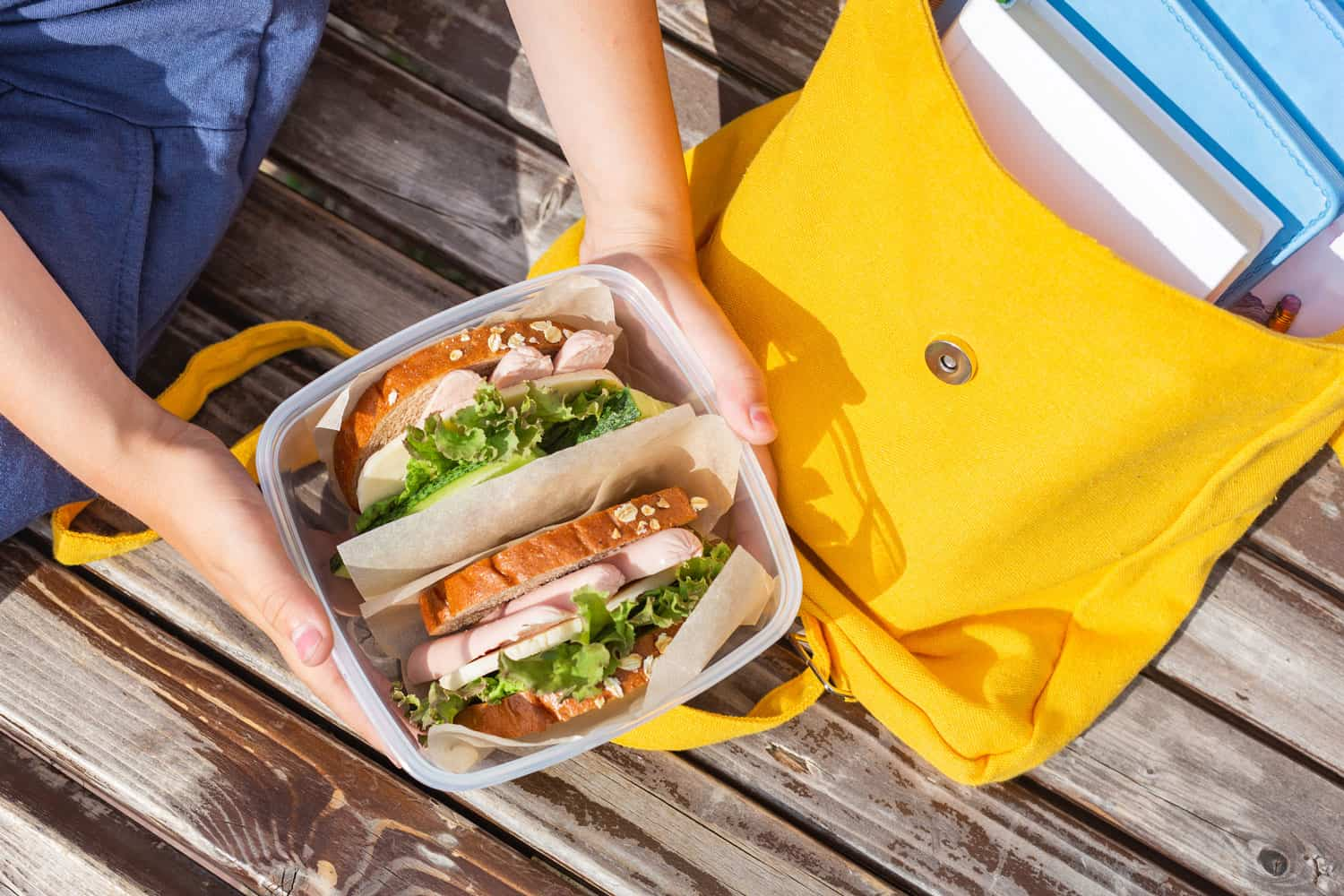 Lunch box in the hands of a child. Sandwiches with bread, lettuce, cucumber and sausages in a plastic container, When Should You Replace Plastic Food Containers?