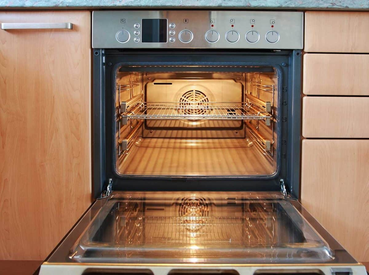Open oven with lights on in kitchen