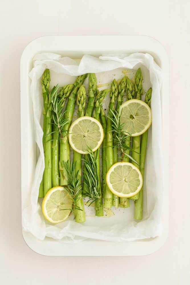 Pieces of celery and sliced lemons on a white tray