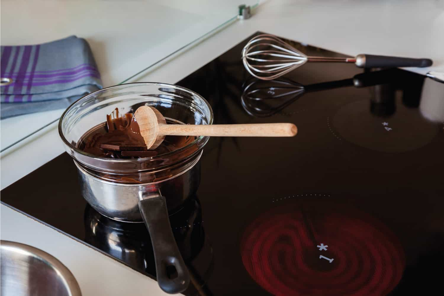 Tempering Delicious Chocolate in a glass bowl and a sauce pan on a induction stove top