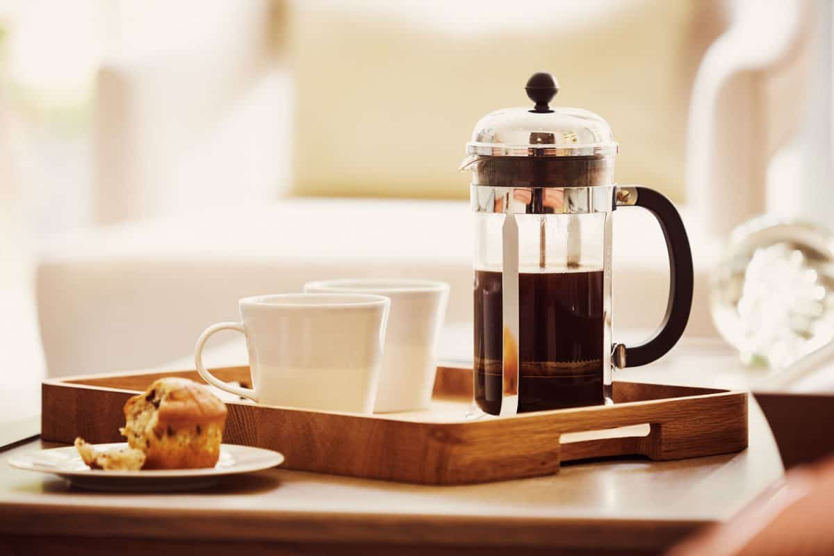Two white coffee mugs and a French press on the side
