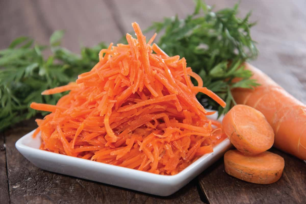 small plate with carrot salad, shredded carrots. How To Shred Vegetables In A Food Processor In 4 Easy Steps