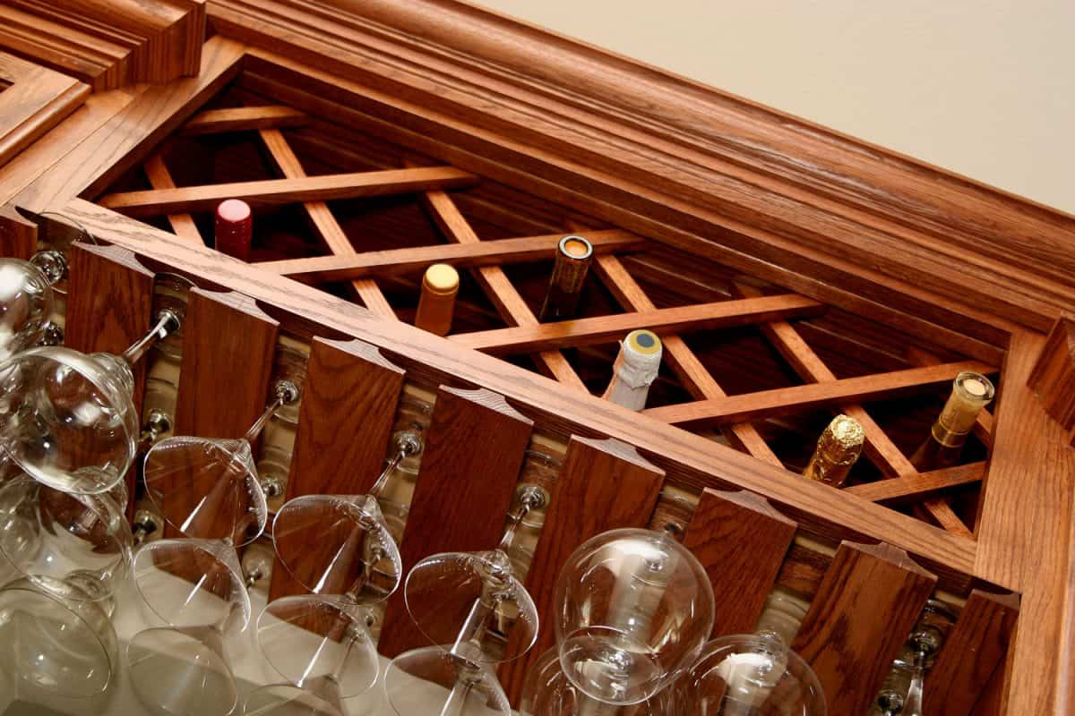 A home bar with glasses hanging and bottles of wine and champagne, How To Store Wine And Cocktail Glasses