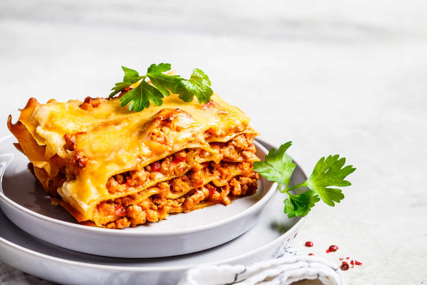 A slice of classic lasagna placed on a small plate, What Temperature Should You Bake Lasagna At? [And What Temperature To Reheat?]