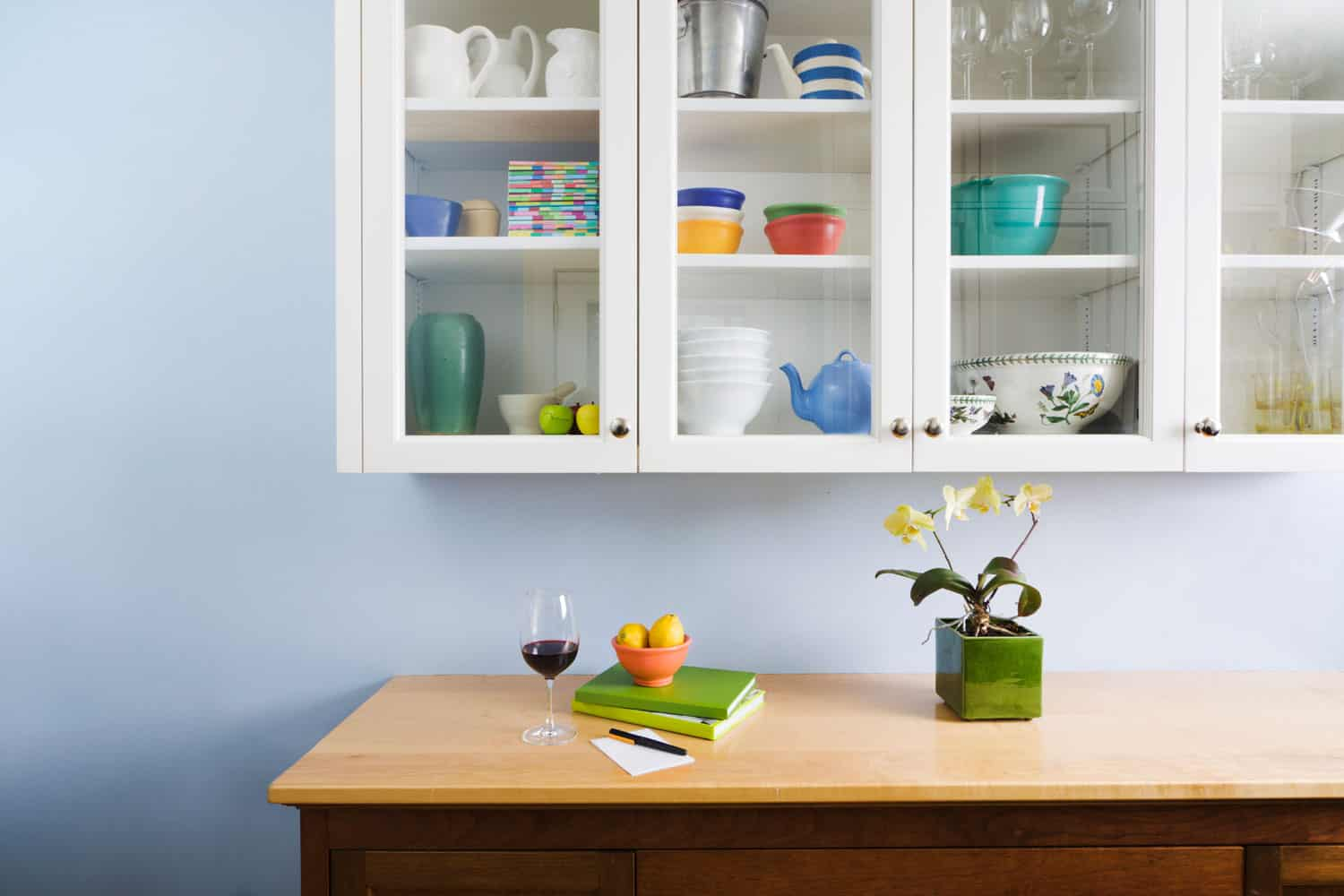 A well-organized kitchen cabinet, counter and cupboard, displaying a glass of wine, books, flowers and housewares in a neat, tidy, freshly painted home interior.