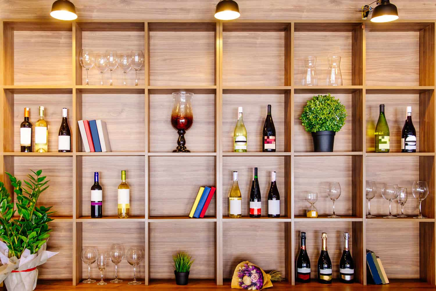 Bottles of white and red wine on a wooden shelf with books in private winery cabinet room