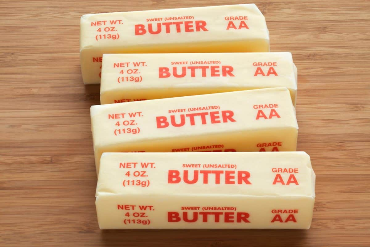 Four unwrapped unsalted butter on a wooden table, Should You Bake With Unsalted Or Salted Butter?