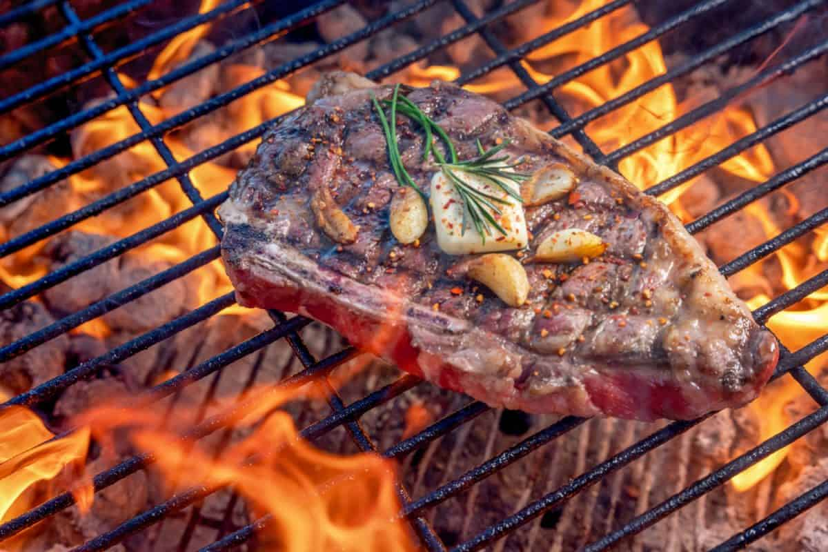Grilled Ribeye Steak On A Hot Charcoal Grill With Flames Topped With Sauteed Garlic Cloves A Pat Of Butter And Rosemary,Should You Add Butter To Steak?