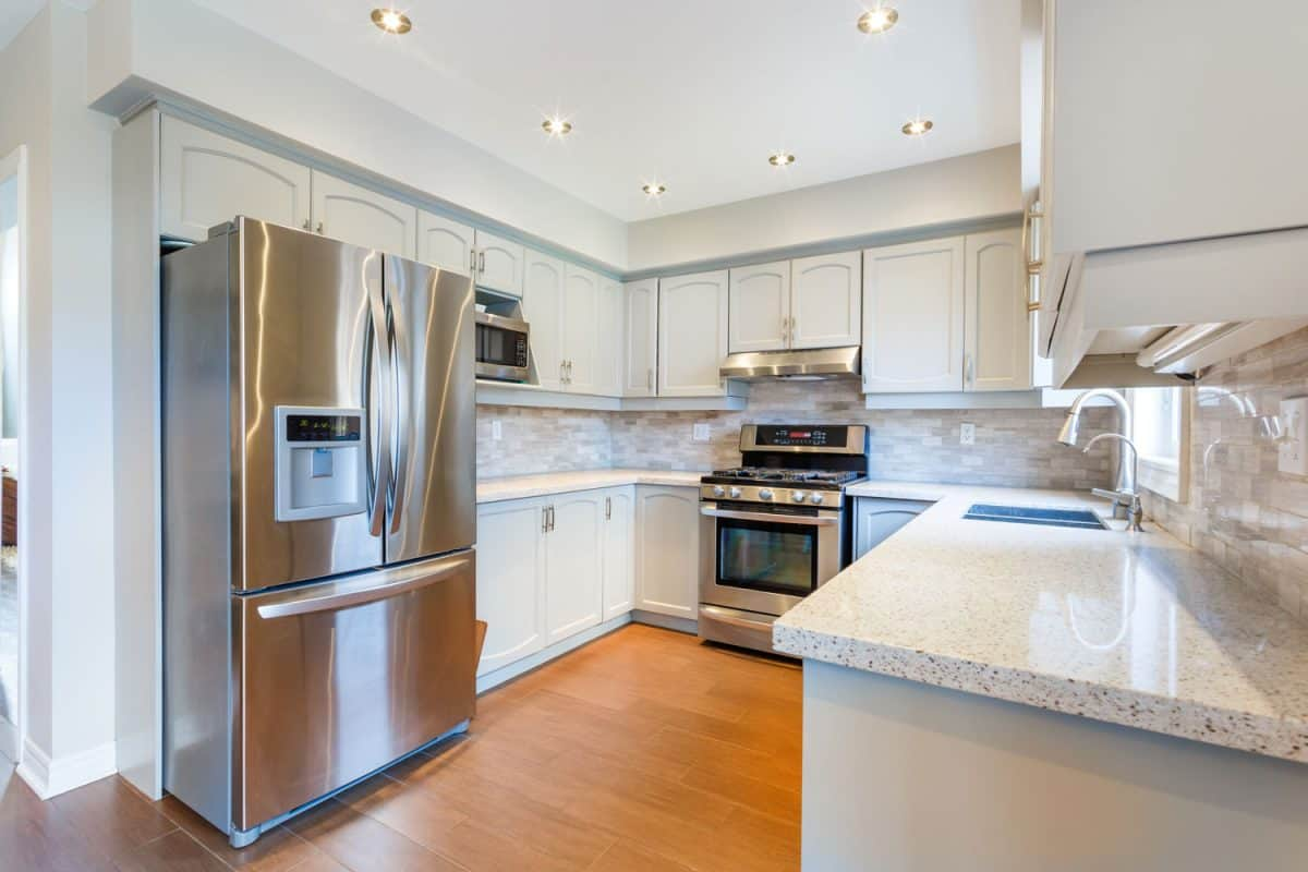 Interior of a gorgeous contemporary inspired kitchen with white marble countertop and a two double door fridge, How To Reset A Samsung Fridge In 4 Steps