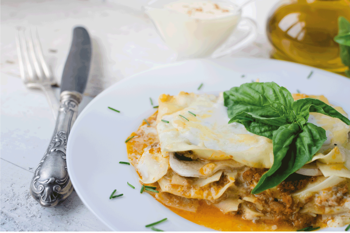 Traditional lasagna made with minced beef bolognese sauce and bechamel sauce topped with basil leaves. Portion of tasty homemade lasagna on white wooden table. Does Lasagna Finish With Pasta Or Sauce