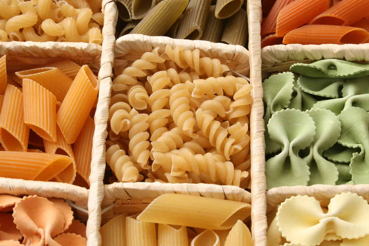 Variety of dried pasta inside container. Shallow depth of field
