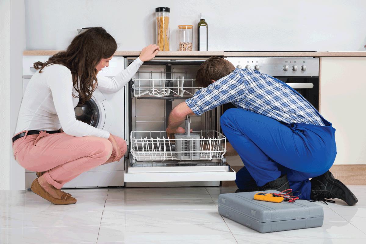 Woman-Looking-At-Repairman-Repairing-Dishwasher.-Samsung-Dishwasher-Won't-Drain---What-To-Do