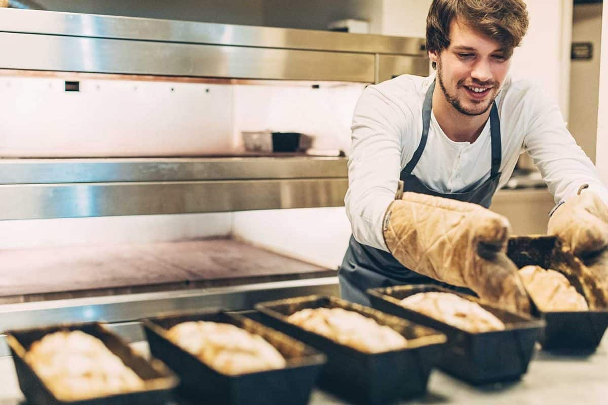 Young baker taking out the hot pans with freshly baked bread