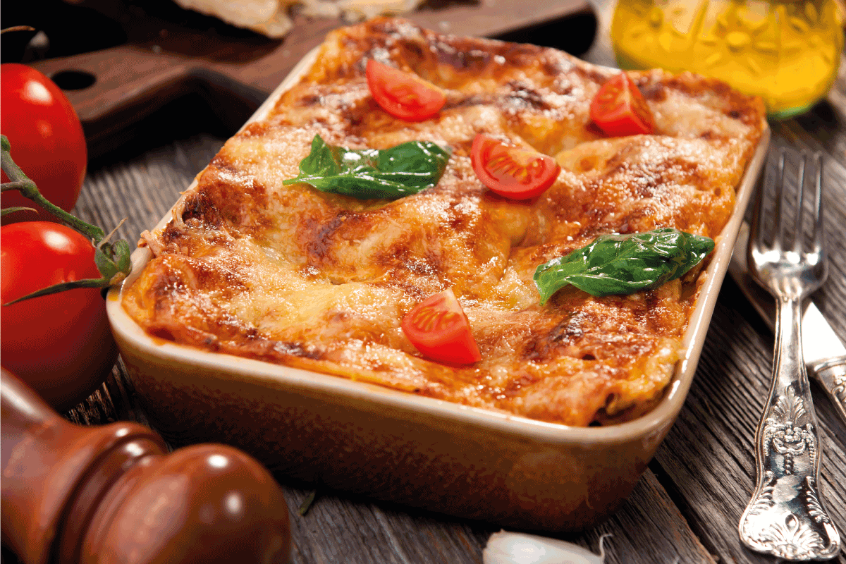 lasagna in a ceramic baking dish with cherry tomatoes on top of wooden table. Should You Defrost a Lasagna Before Cooking it