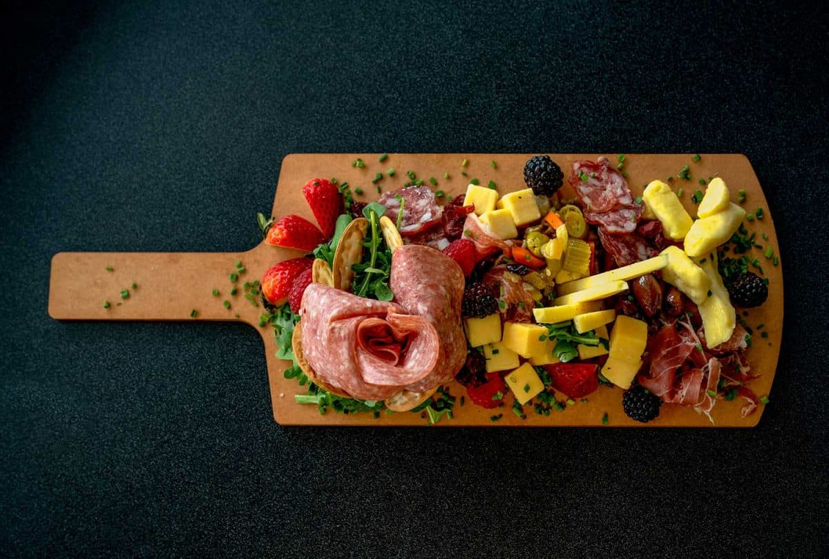 A charcuterie platter arranged with a variety of meats, cheeses and fruit