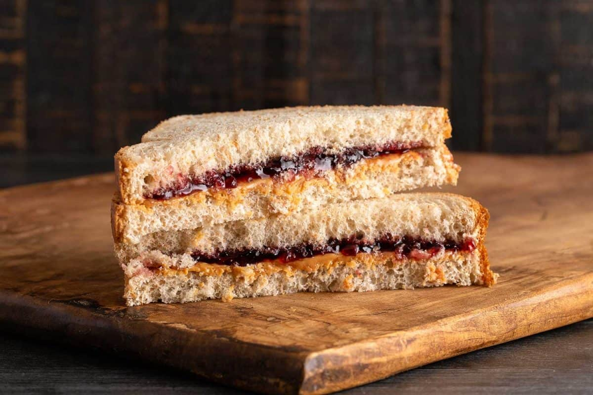 A peanut butter and grape jelly sandwich on a wooden cutting board