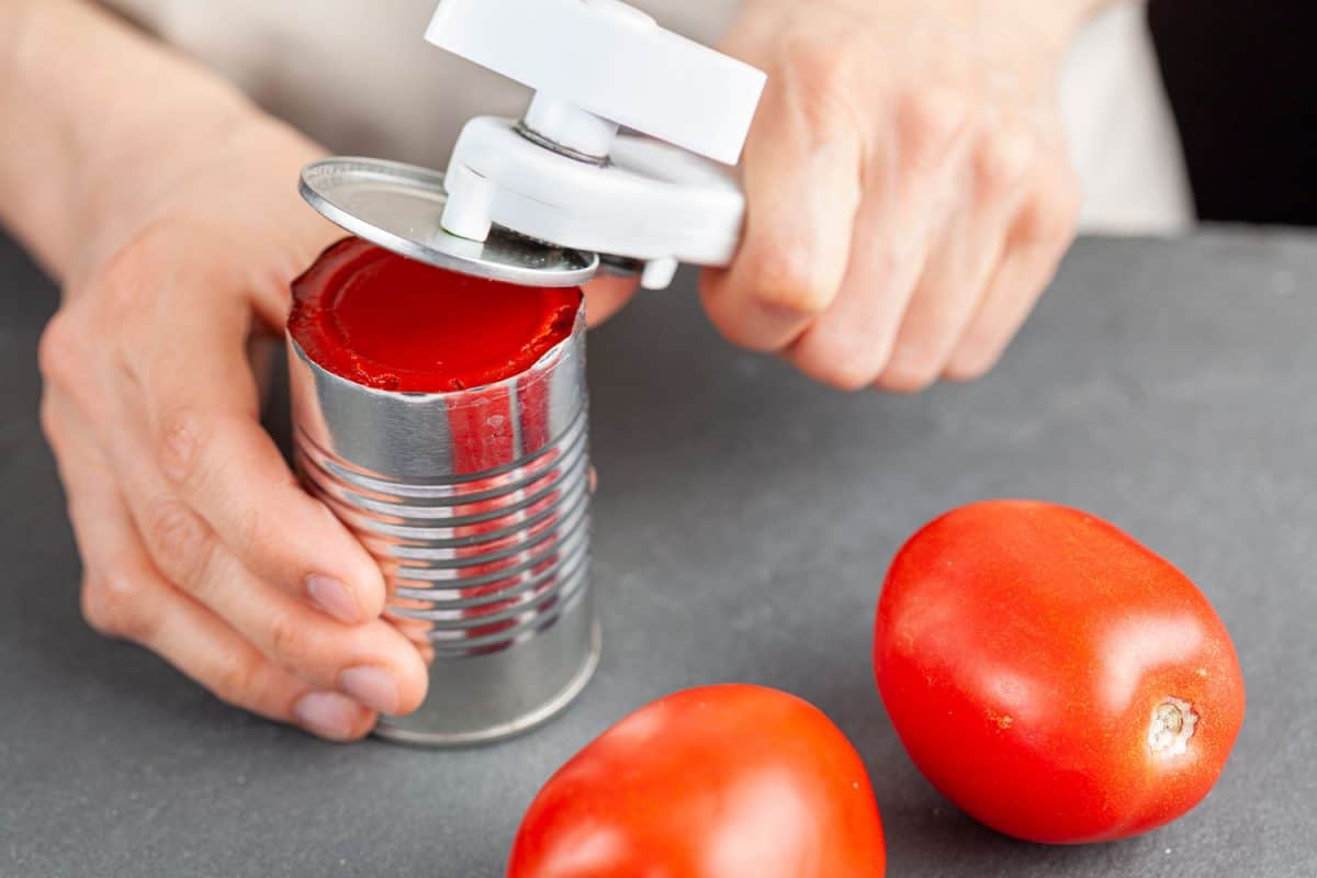 A woman is carefully opening a can of tomato paste on a kitchen counter using a white plastic can opener, How To Use A Pampered Chef Can Opener
