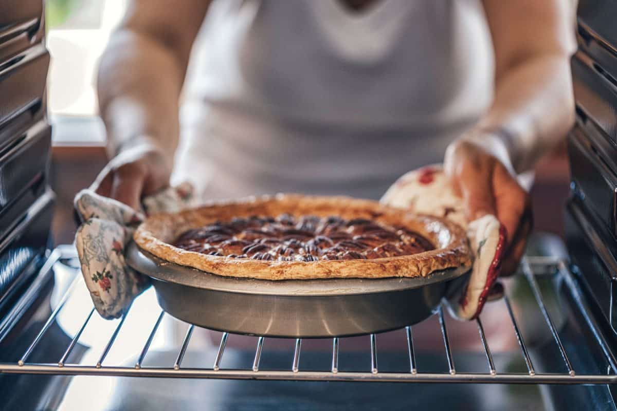 A woman taking off a freshly baked pecan pie out of the oven, Does Flour Burn In The Oven?
