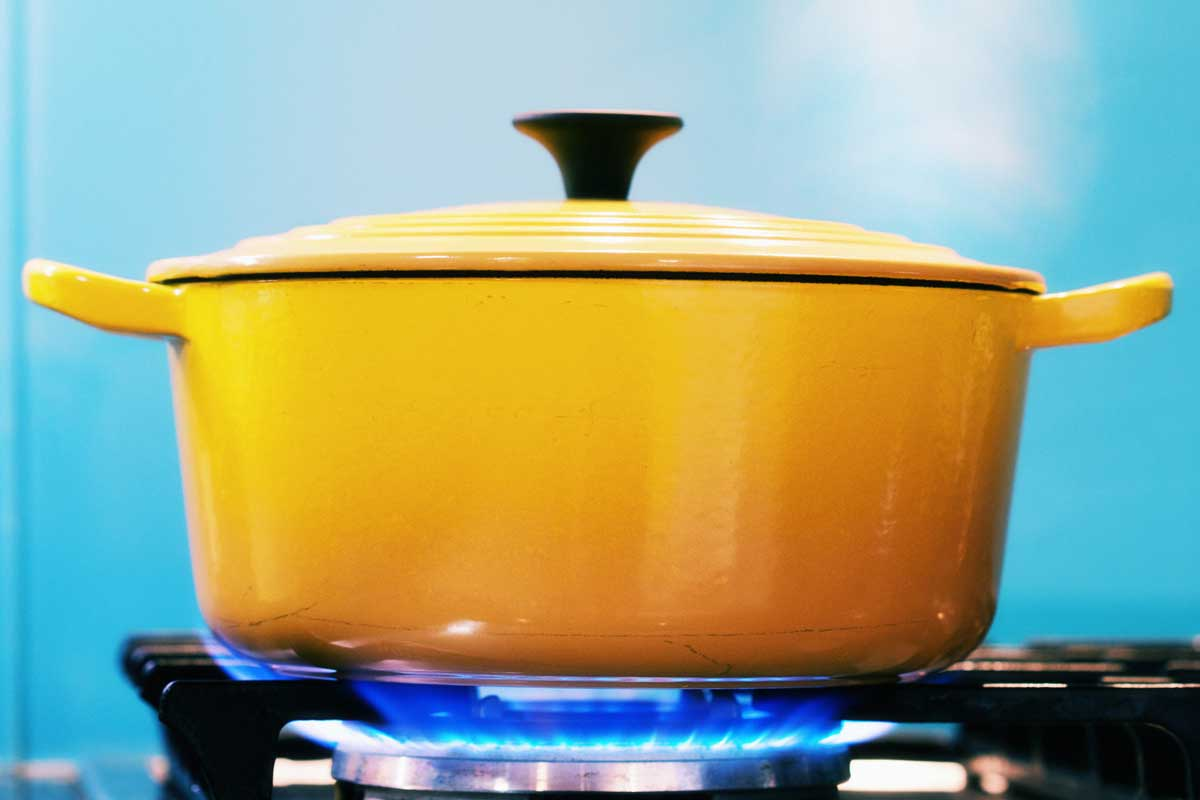 A yellow enamel casserole with its lid on, sits on a lit gas burner creating steam as it heats, Can Le Creuset Ceramic Go On The Stove?