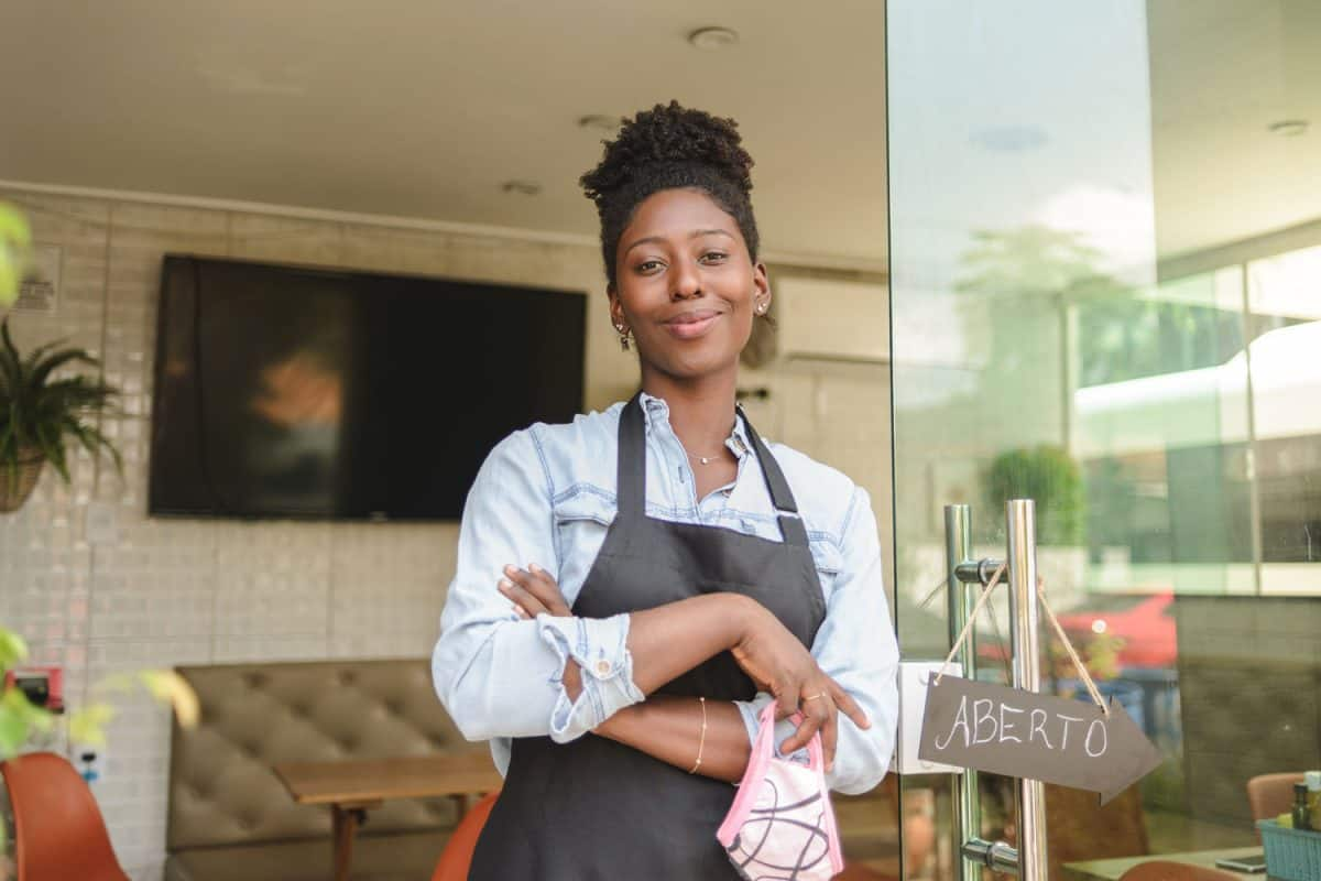 A young restaurant owner wearing an apron standing on the exit, Are Aprons One Size Fits All?