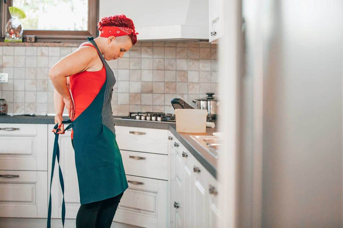 Adult woman in domestic kitchen putting apron on