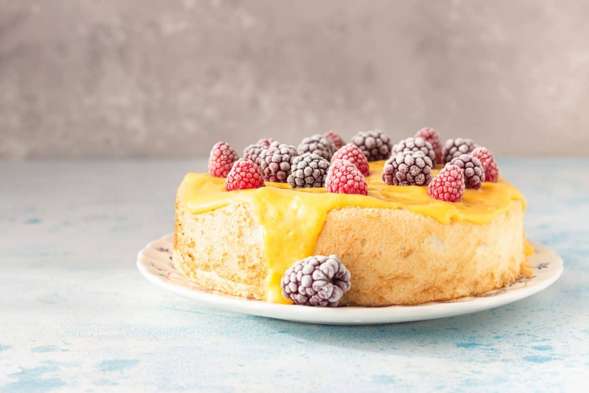 Angel food cake with lemon curd and frozen berries (raspberry and blackberry) on a plate, blue concrete background, What Flour To Use For Angel Food Cake?
