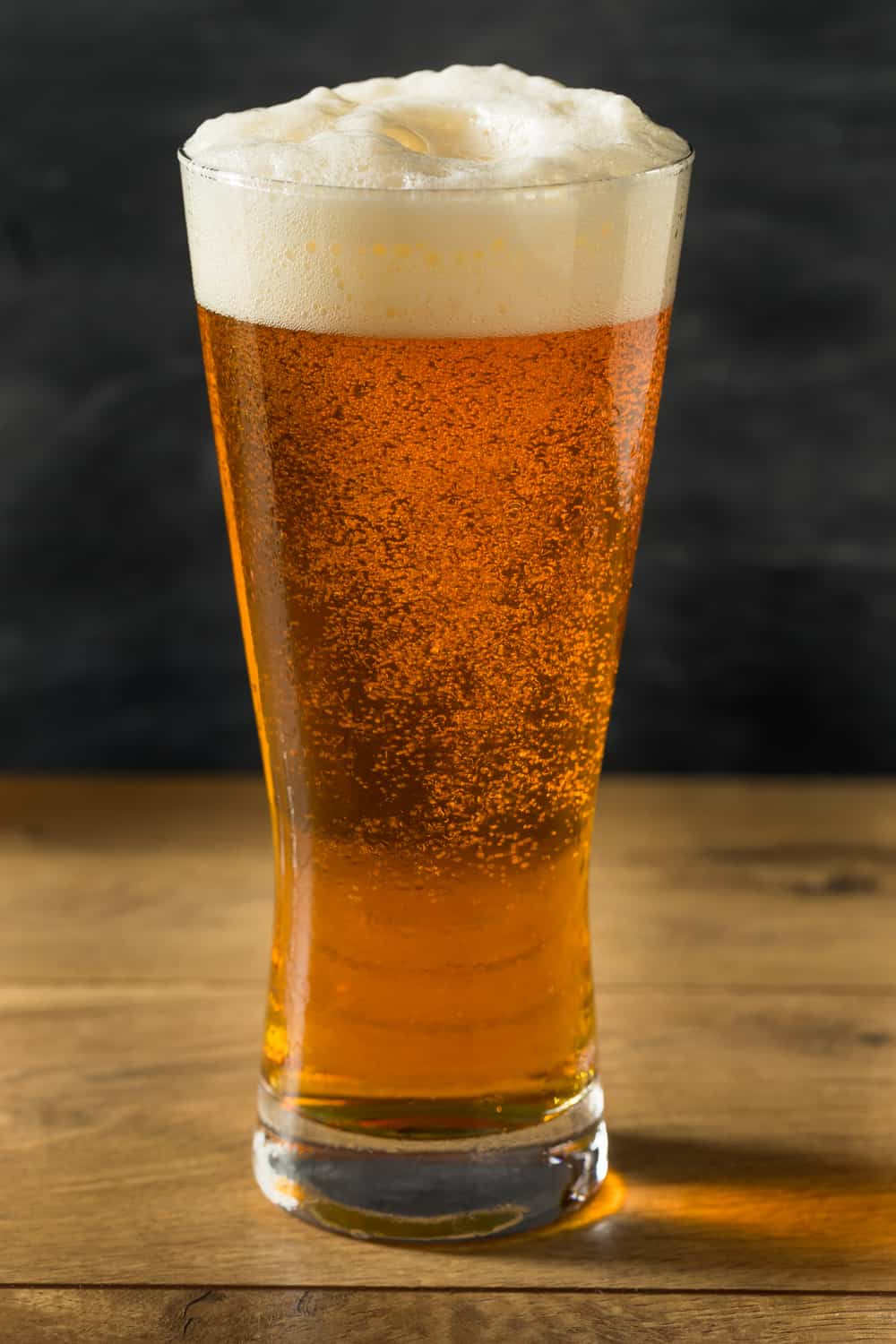 Boozy Golden Beer Ale in a Tall Glass with Foam