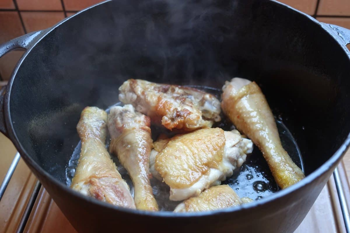 Chicken thighs being cooked in a cast iron casserole dish