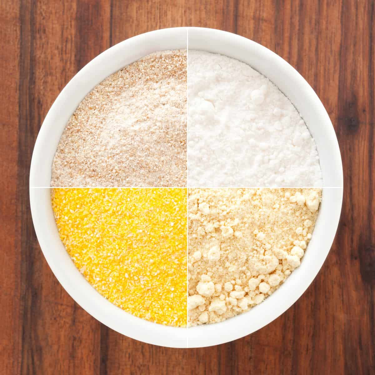 Composite of several shots of flours (wholemeal, regular, corn, soy) in white bowl for variation concept