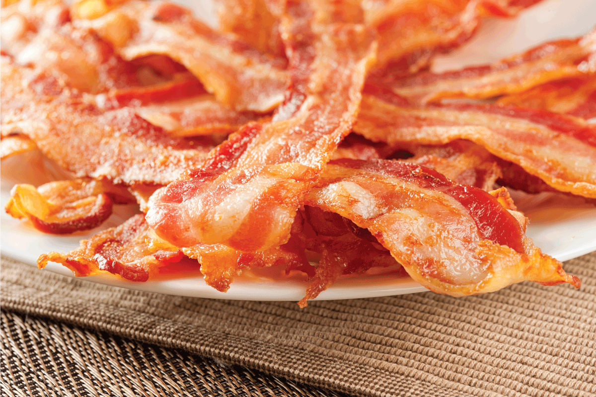 Cooked Greasy Bacon on a plate. Does Microwaving Bacon Reduce Fat And Calories