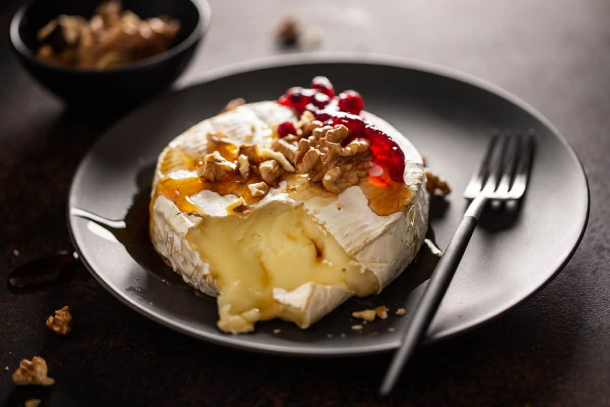 Delicious microwaved brie cheese garnished with nuts and cranberries, Can You Microwave Brie Cheese?