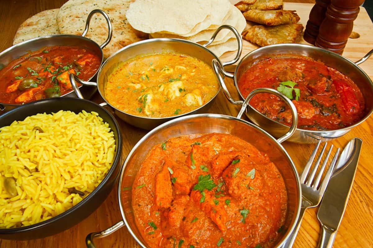 Different kinds of Indian cuisines placed on top of a wooden table