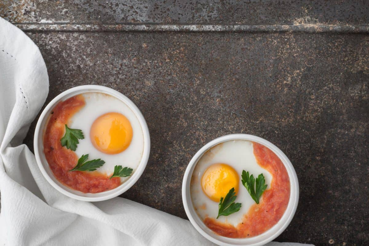 Eggs backed with tomatoes and parsley in the ramekins on the metal table top view horizontal