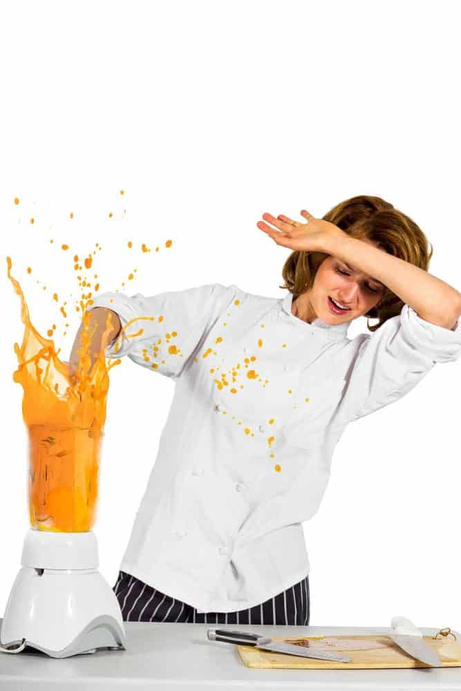Female chef making a mess with a blender