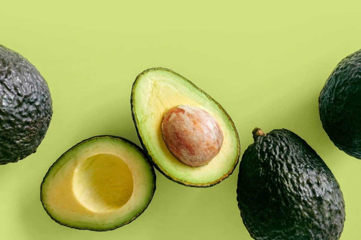 Fresh organic hass avocados on a green background, top view with copy space, Does Microwaving An Avocado Soften It?